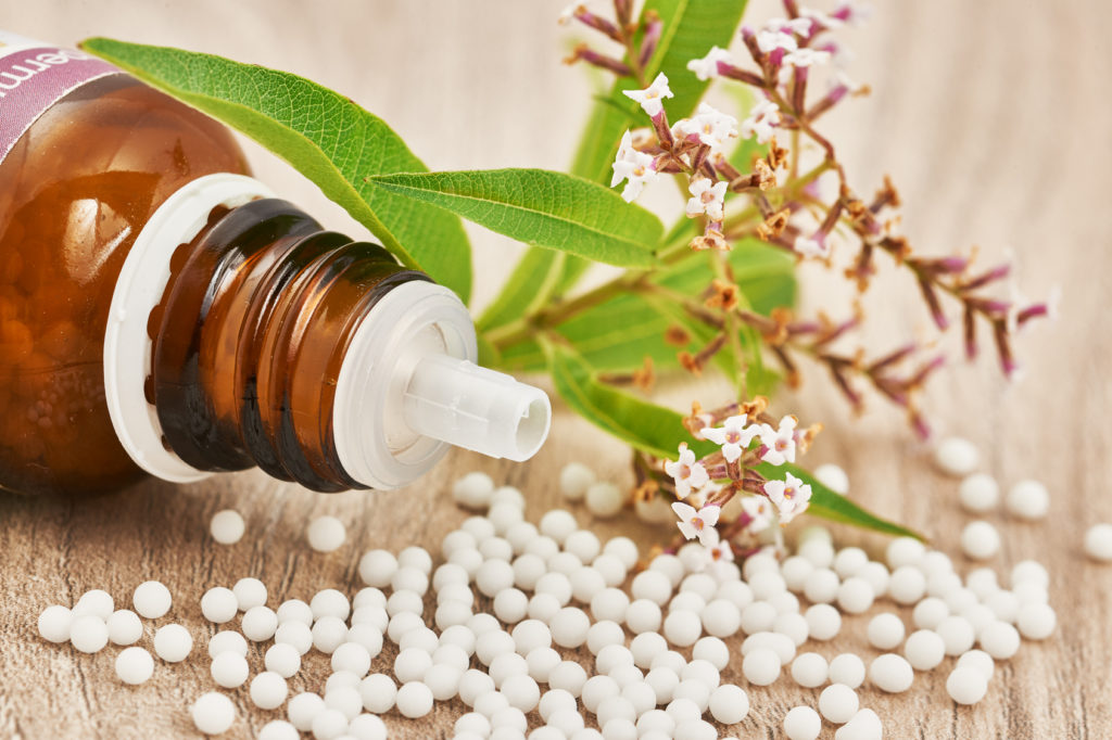 Homeopathic granules scattered around a glass bottle and a medicinal herb on a wooden table